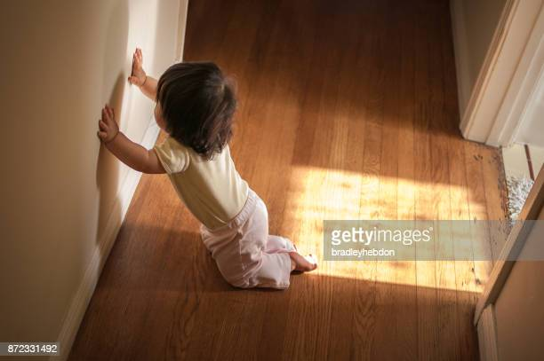 Baby girl looking at her shadow on a wall