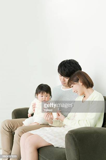 Baby girl looking at mobile phone with parents on sofa