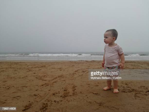 Baby Girl Looking Away While Standing At Beach