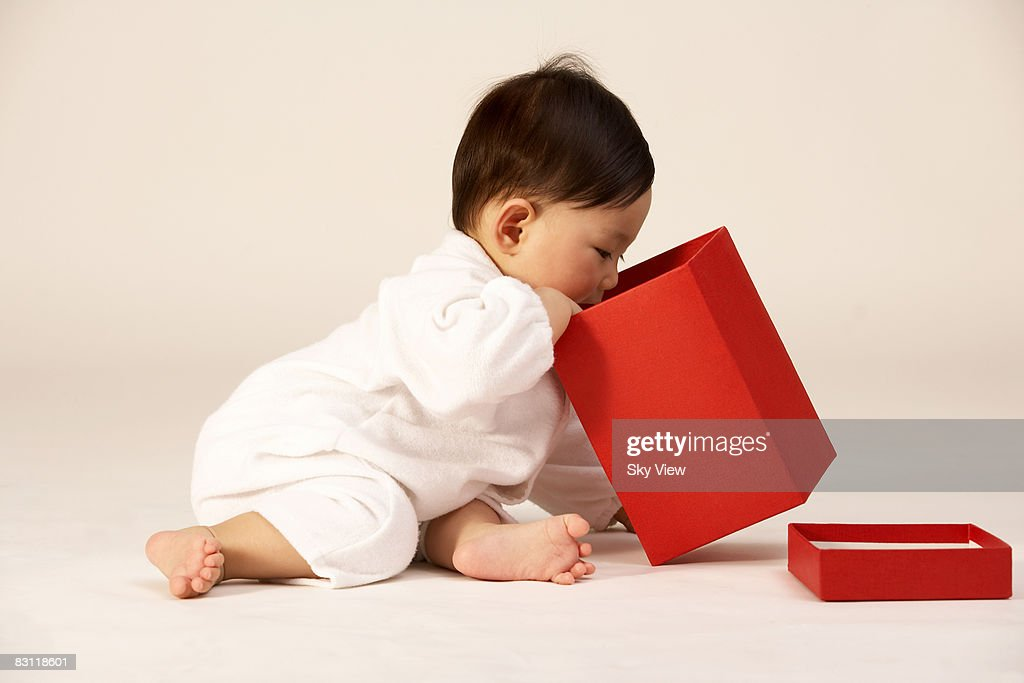 Baby girl (6-9 months) looking in box : Stock Photo