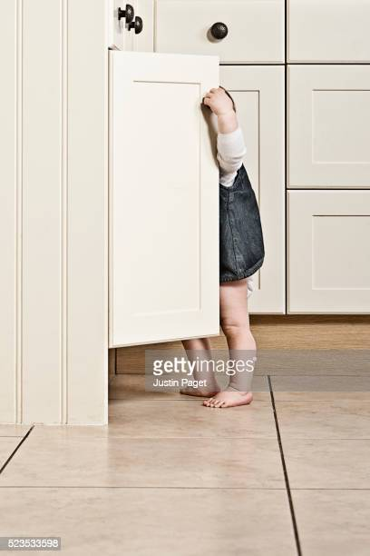 Baby Girl Looking into Kitchen Cupboard