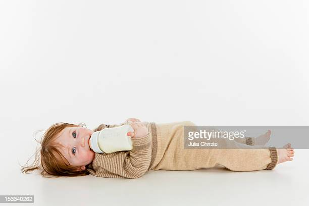 A baby girl lying down with a bottle of milk