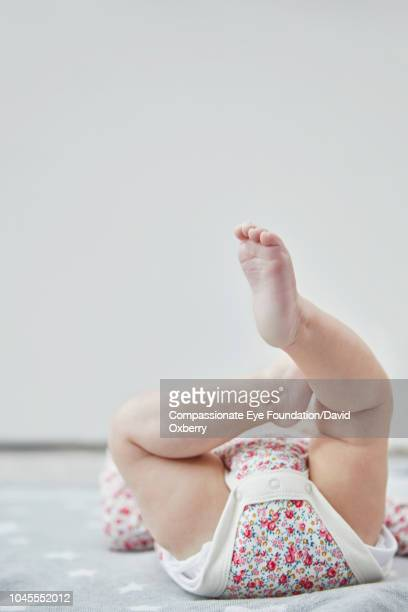 Baby girl lying down with legs up
