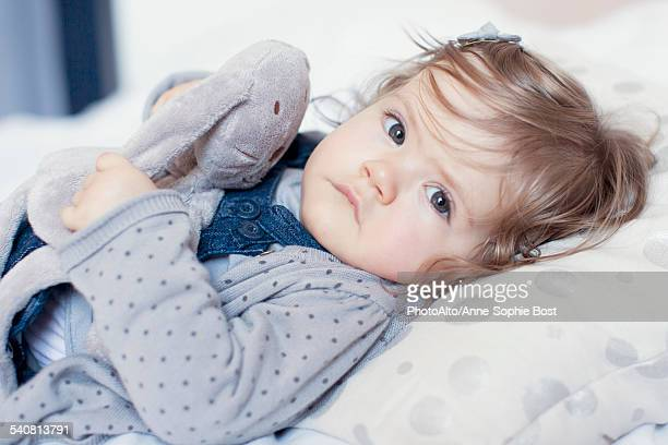 Baby girl lying down with stuffed toy, portrait