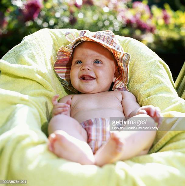 Baby girl (3-6 months) lying in cradle outdoors, smiling, close-up