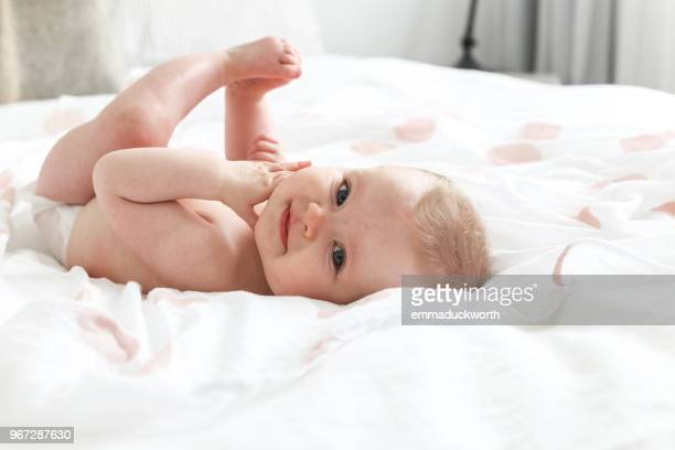 baby girl lying on a bed - windel stock-fotos und bilder