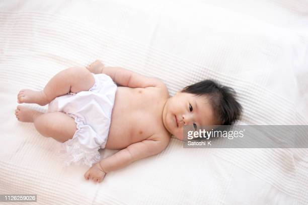 baby girl lying on back in living room - lying on back stock pictures, royalty-free photos & images