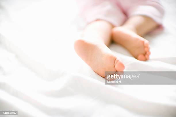 Baby girl (15-18 months) lying on bed, close up of feet