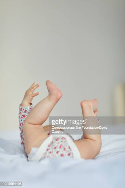 Baby girl lying on bed with legs up