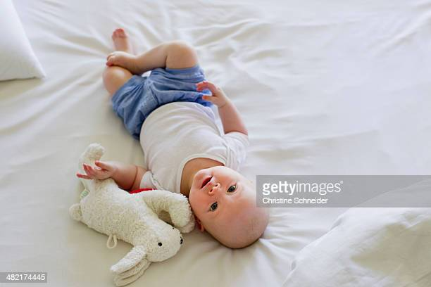Baby girl lying on bedclothes with soft toy