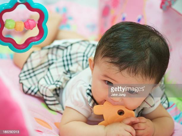 Baby girl lying on belly and chewing teething toy