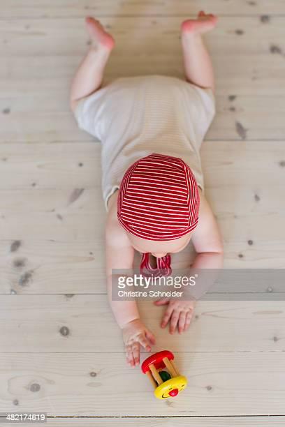 Baby girl lying on floor with toy