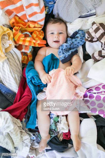 baby girl lying on laundry - surrounding stock pictures, royalty-free photos & images
