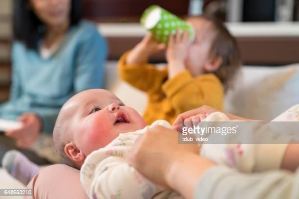 Babymädchen Mutter lachen Knie liegend