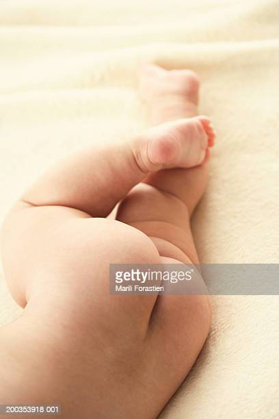 Baby girl (3-6 months) lying on side, low section, close-up