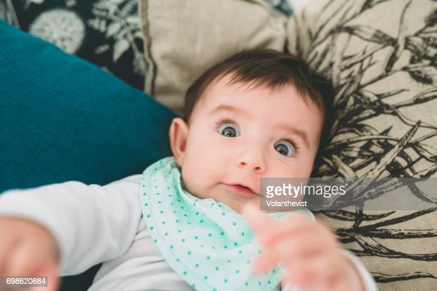 Baby girl lying on the couch with surprised funny face