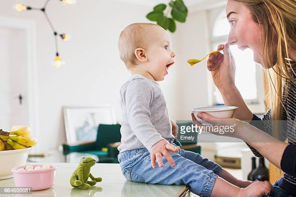 baby girl mimicking mother whilst eating at kitchen table - essen mund benutzen stock-fotos und bilder