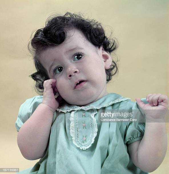 A baby girl of 7monthsold one hand on cheek wearing a green dress 22nd April 1948
