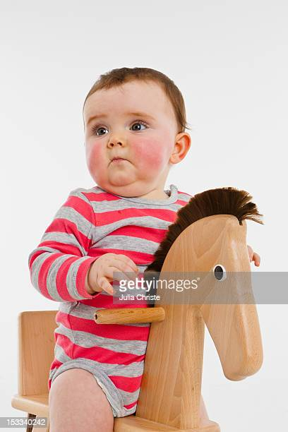 a baby girl on a rocking horse - rosy cheeks stock pictures, royalty-free photos & images