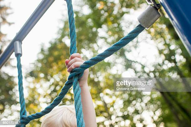 baby girl on climbing frame at park, focus on hand - ジャングルジム ストックフォトと画像