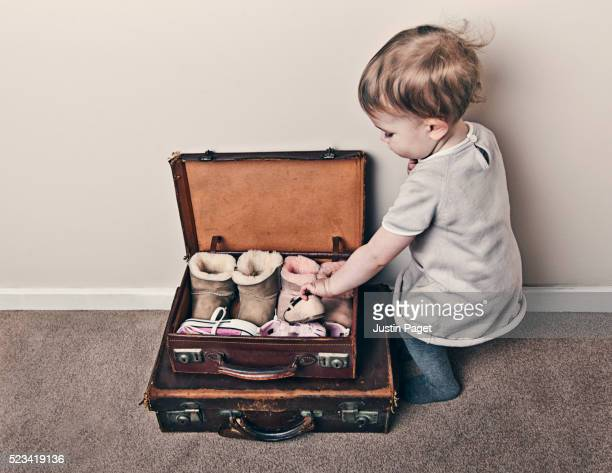 Baby Girl Packing Favourite Shoes into Suitcase