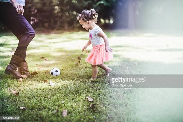 Baby girl playing ball in garden