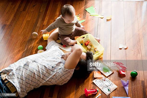 Baby Girl Playing by Lying Father