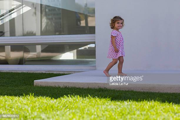 Baby girl playing in backyard of the house