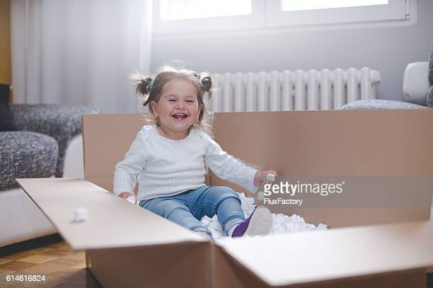 baby girl playing in box with styrofoam pellets - calientes fotografías e imágenes de stock