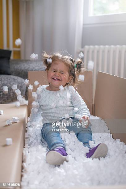 baby girl playing in box with styrofoam pellets