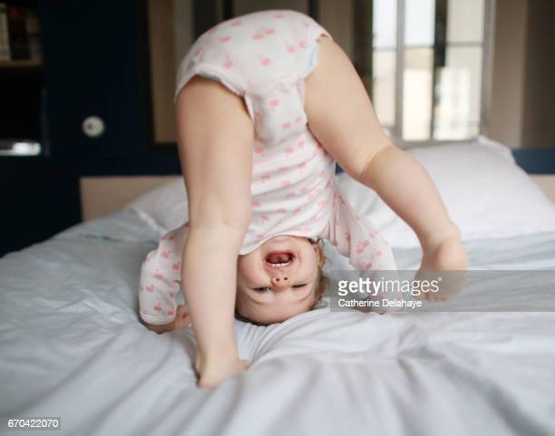 A baby girl playing on a bed
