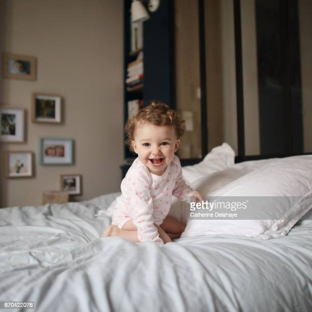 a baby girl playing on a bed - bébé stock photos and pictures