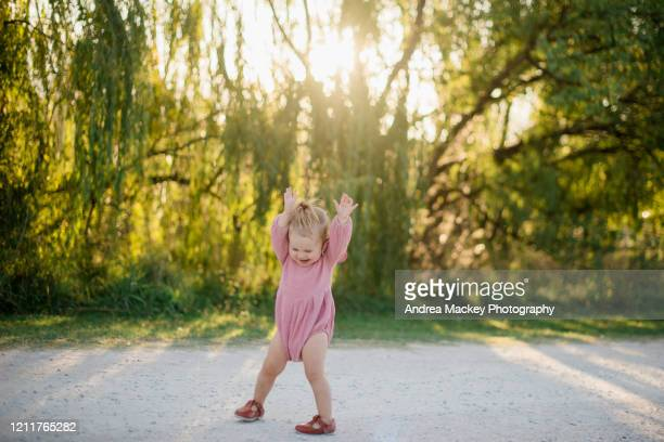 baby girl playing on dirt road at sunset - toddler stock pictures, royalty-free photos & images
