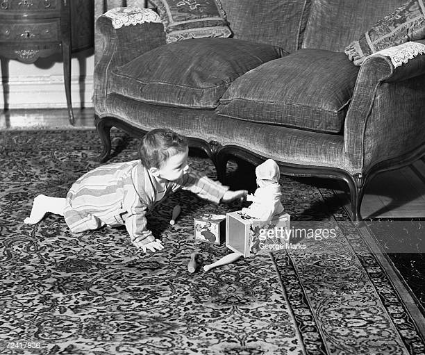 baby girl (6-9 months) playing on floor, (b&w) - jack in the box stock photos and pictures