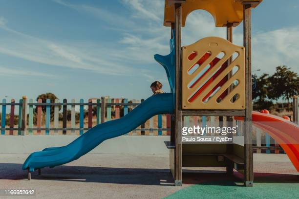 baby girl playing on slide at playground against cloudy sky - playground stock pictures, royalty-free photos & images