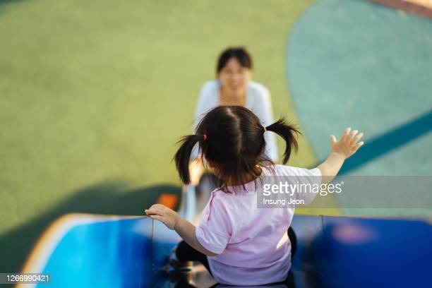 baby girl playing on slide in playground - south korea stock pictures, royalty-free photos & images