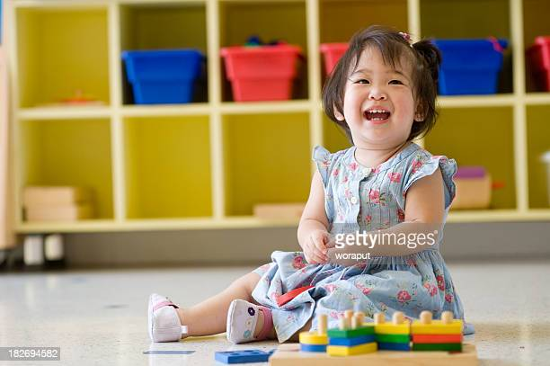 Baby girl playing on the floor in a nursery place