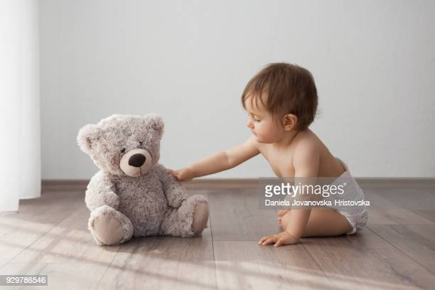 baby girl playing on the floor with teddy bear
