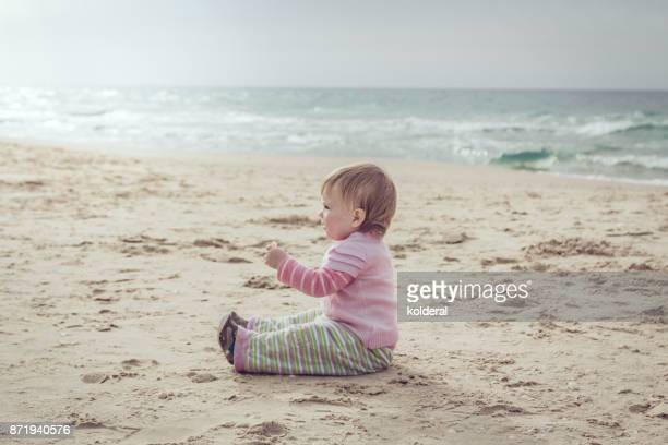 baby girl playing on the Mediterranean beach during sunset