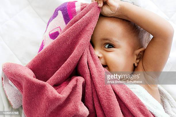 Baby girl playing peek a boo with a pink towel