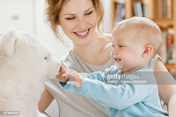 baby girl playing with a teddy bear and laughing - mama bear stock photos and pictures