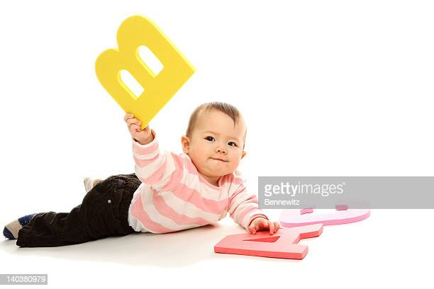 Baby girl playing with big colorful letters