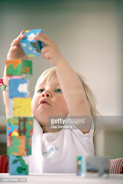 Baby girl (15-18 months) playing with building blocks, close-up