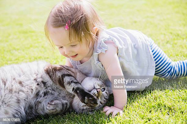 Baby girl (6-11 months) playing with cat