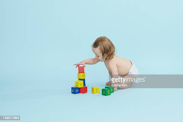 baby girl playing with colored blocks - baby toys stock photos and pictures