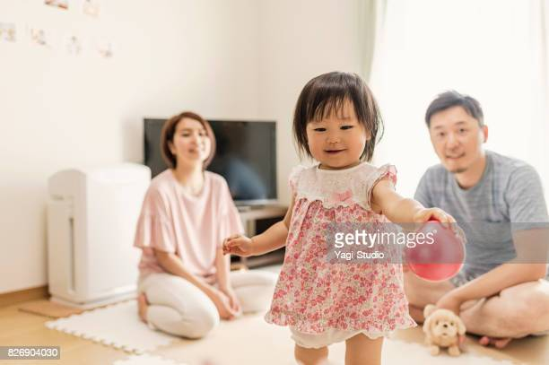 Baby girl playing with family in home