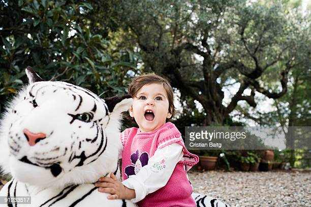 Baby girl playing with her stuffed tiger toy