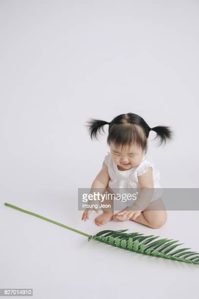 Baby girl playing with palm leaves