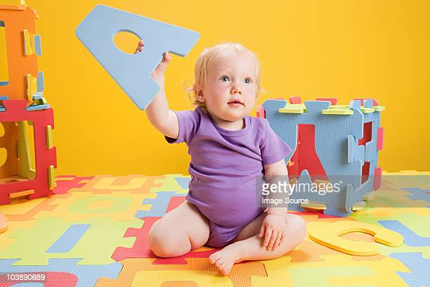 Baby girl playing with toy alphabet letters