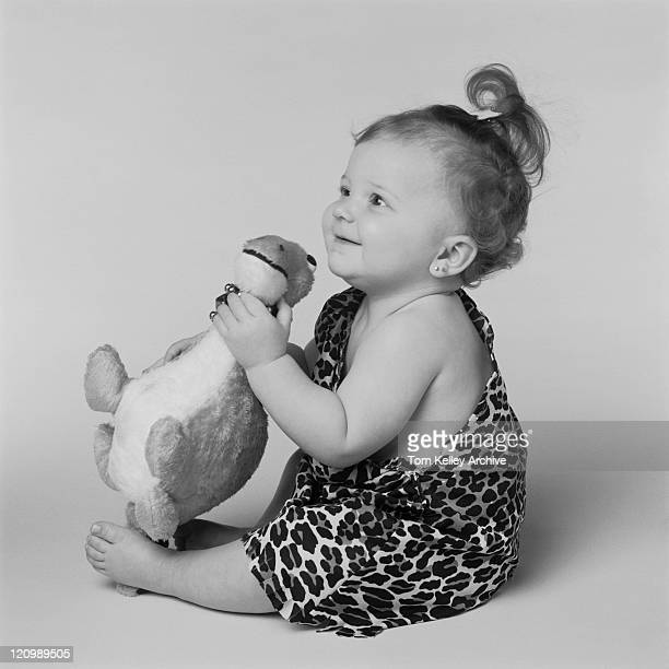 Baby girl playing with toy dinosaur, smiling